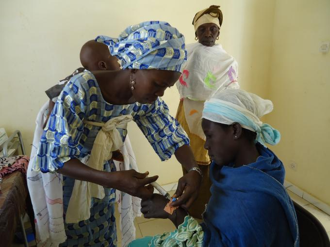 A health facilitator injecting medicine to a pregant woman in Patar health post in Fatick Region